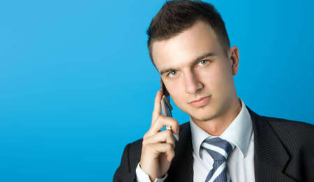 Attractive young businessman in black suit with mobile phone. More similar in my portfolio Stock Photo - 1216434