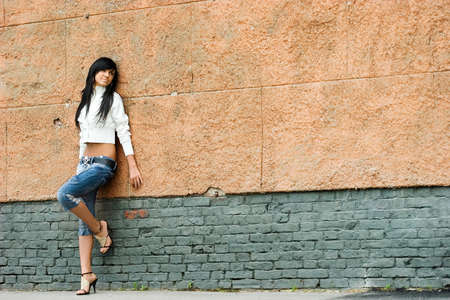 Sad and Pretty Girl standing alone near grunge wall Stock Photo - 1413415