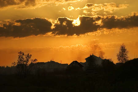suburbian: Evening summer sun  in clouds and suburbian landscape under it