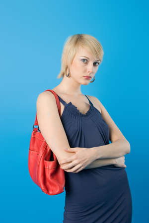 Pretty fashion woman  posing with red purse. photo