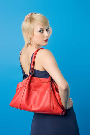 Pretty fashion woman  posing with red purse photo
