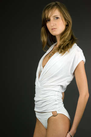 Young fashion model with slender figure posing in white stylish clothes Stock Photo - 1441083