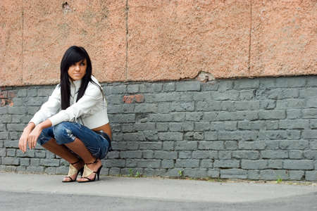 Sad and Pretty Girl standing alone near grunge wall Stock Photo - 1497610