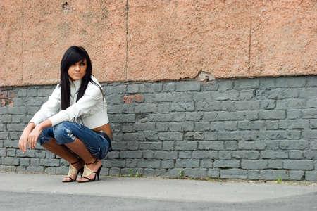 Sad and Pretty Girl standing alone near grunge wall Stock Photo - 1497610