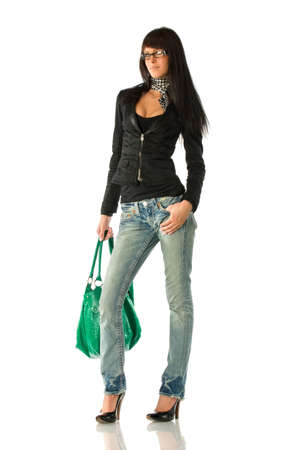 Young stylish brunette in glasses posing with green purse. Isolated over white photo