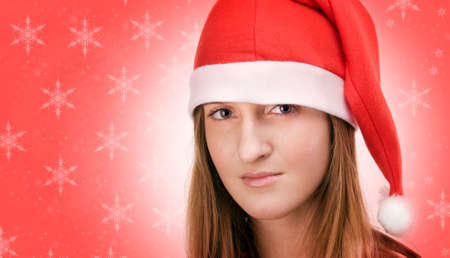 Young girl in santa's cap with beautiful sad eyes  posing over red background with snowflakes Stock Photo - 2240937