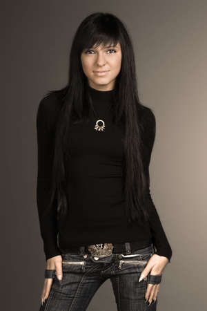 Young and fashionable brunette  posing in black stylish sweater and jeans photo
