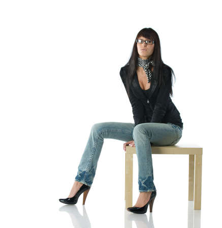 Young stylish brunette in glasses sitting on the modern table. Isolated over white photo