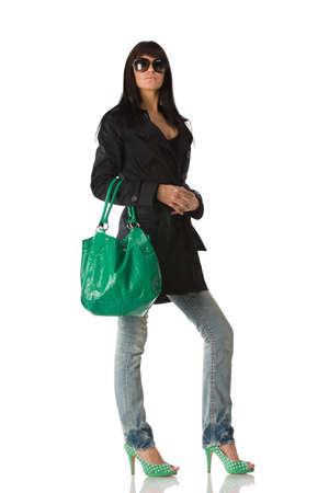 Young stylish brunette in sun glasses posing with green purse. Isolated over white photo