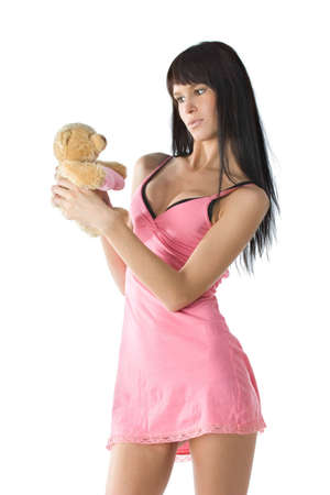 Young girl in pink dress playing with her toy bear photo