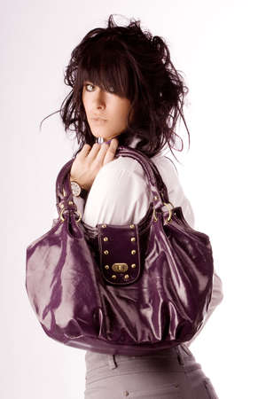 Young stylish brunette posing with violet purse. Isolated over white Stock Photo