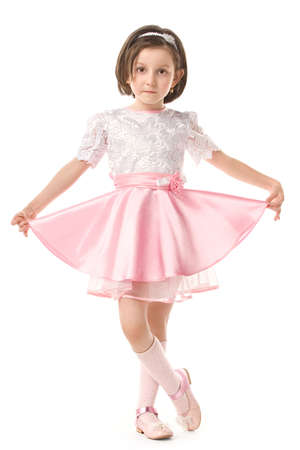 only 1 girl: The lovely little girl posing in a beautiful pink dress. Isolated over white background