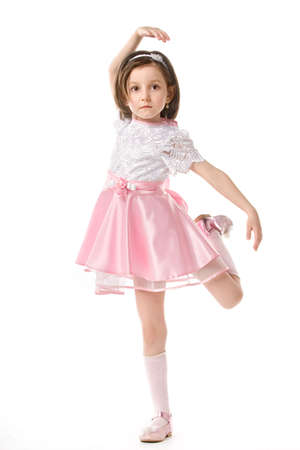 The lovely little girl posing in a beautiful pink dress. Isolated over white background