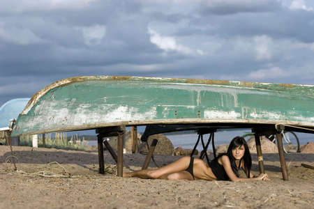 Young sexy woman laying under the old boat on the beach photo