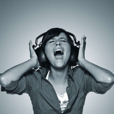 Young woman in headphones screaming. Blue toned version Stock Photo - 3481845