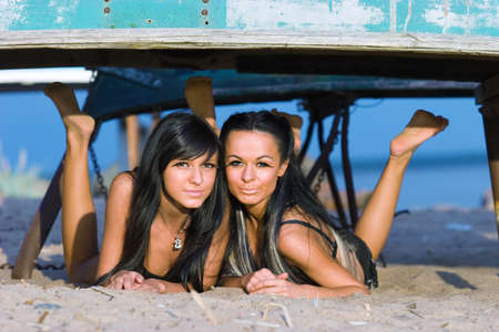 Two beautiful girls laying on the beach under the old boat photo