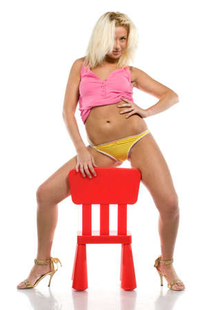 Playful blonde with toy chair. Isolated over white. photo