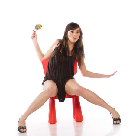 Young and beautiful woman sitting on a toy chair. Isolated over white photo