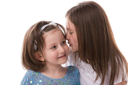 Two sisters whispering secrets to each other photo