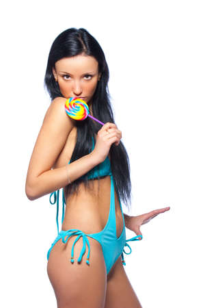 Young glamourous and sexy woman posing in blue swimsuit with lollipop. Isolated over white background photo