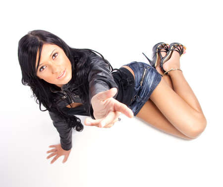 Young brunette posing in short skirt. Isolated over white background photo