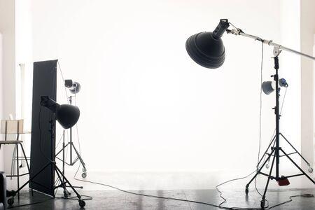 Foto di uno studio fotografico a vuoto con le moderne apparecchiature di illuminazione. Spazio vuoto per il testo o gli oggetti.