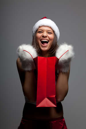 Beautiful sexy girl wearing santa claus clothes with paper gift bags in hands photo