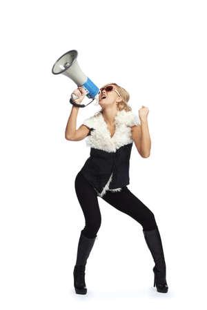 Young blonde woman  shouting through  megaphone photo
