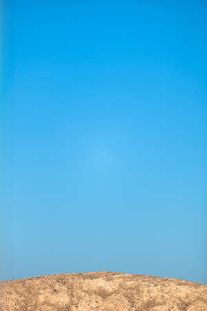Heap of sand and clear blue sky photo