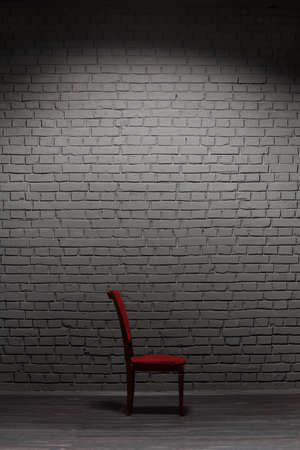 Old wooden chair near the grey brick wall