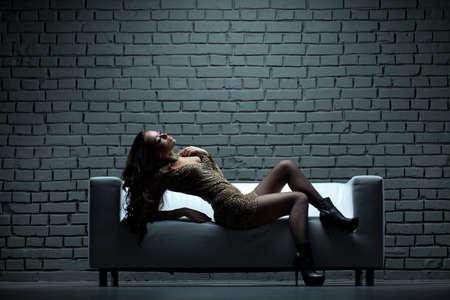Beautiful model in gala dress laying on sofa
