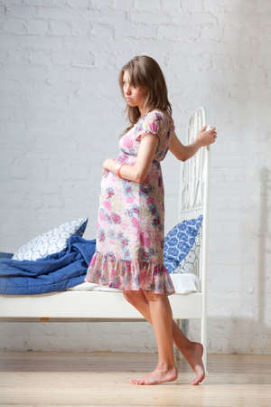 worries: Young pregnant woman standing near the bed