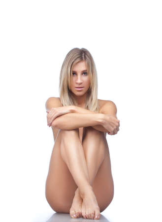 Beautiful naked blonde woman sitting on the floor. Isolated over white. photo