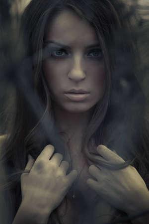 Giovane e bella donna in topless posa all'aperto. Scuro misterioso ritratto artistico.
