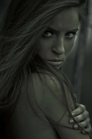 Beautiful young topless woman posing outdoors. Dark mysterious artistic portrait. photo