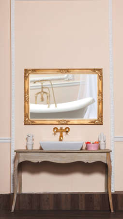 Luxury washstand and golden faucet with mirror. photo
