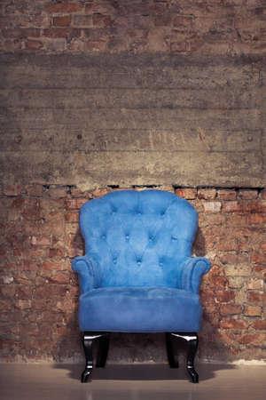 An antique blue velvet chair near the grungy brick wall Stock Photo