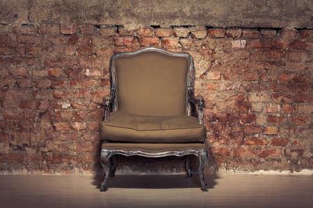 Antique chair against a grungy brick wall photo
