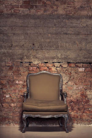 Antique chair against a grungy brick wall Stock Photo