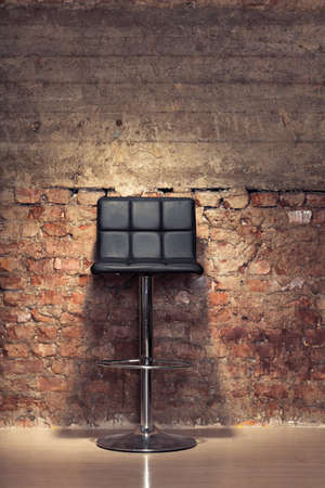Modern stylish black chair against a grungy brick wall photo