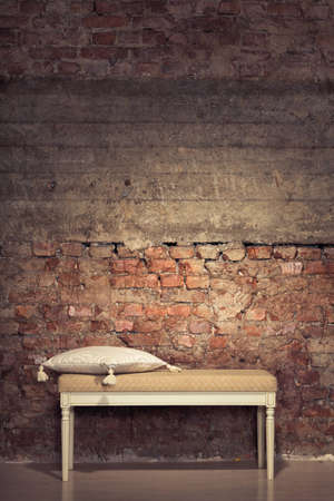 Antique chair against a grungy brick wall photo