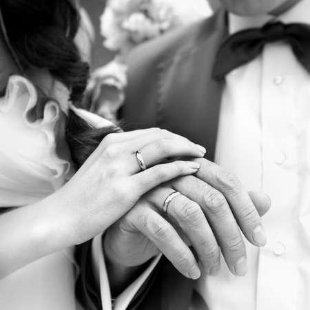 Hand van de bruidegom en de bruid met trouwringen. Zwart-wit beeld.