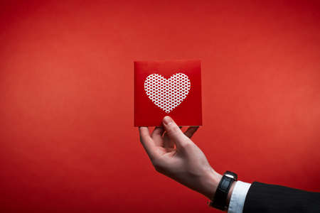 beloved: Male hand holding red Valentines card with heart on a pink background Stock Photo