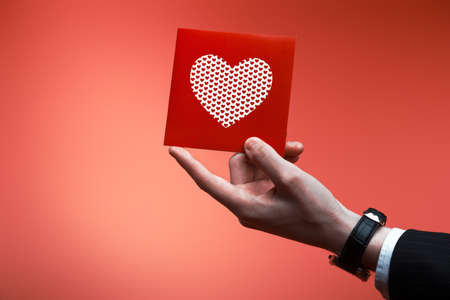 Male hand holding red Valentines card with heart on a pink background Stock Photo - 12197473