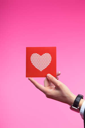 Male hand holding red Valentines card with heart on a pink background Stock Photo - 12197474