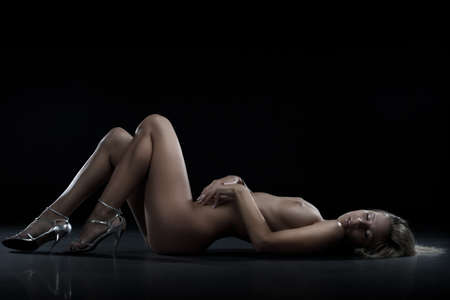 Sensual blonde woman lying on the floor in studio. Full lenght portrait Stock Photo