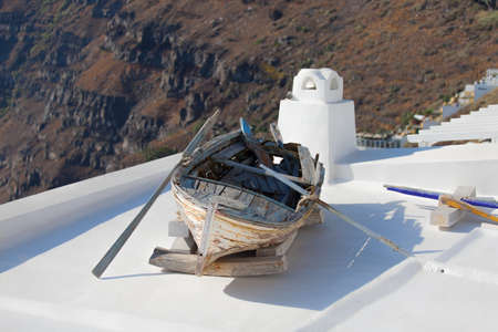 Old fishing row boat on the roof in Fira, Santorini island, Greere photo