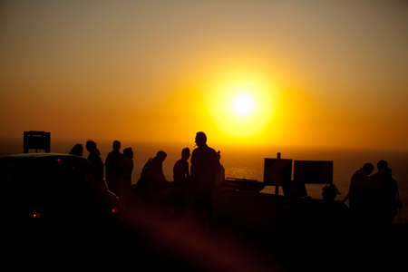 Silhouettes of people watching sutset near the sea, Santorini, Greece photo