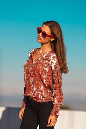 Young stylish woman in red sunglasses photo