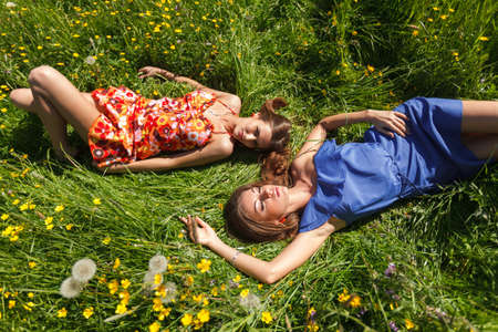 sun down: Two beautiful girls resting in the grass on a summer day